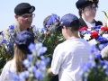 General Curtis M. Scaparrotti, Supreme Allied Commander Europe, receives a wreath from a French child to be placed on the Iron Mike Memorial during the Iron Mike Ceremony in La Fiere France, June 3, 2018.